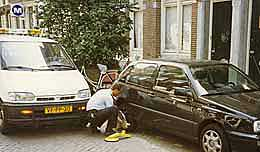 An Amsterdam police officer places a wheel clamp on an illegally parked car.