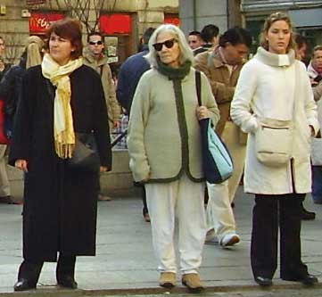 Three women wait for traffic to clear before crossing a street in Madrid.