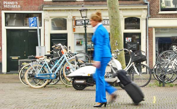 A KLM flight attendent with rolling bag and hand bag going to Amsterdam's Schiphol Airport.