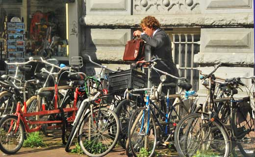 A young fellow on his way to work in Amsterdam parks his bike.