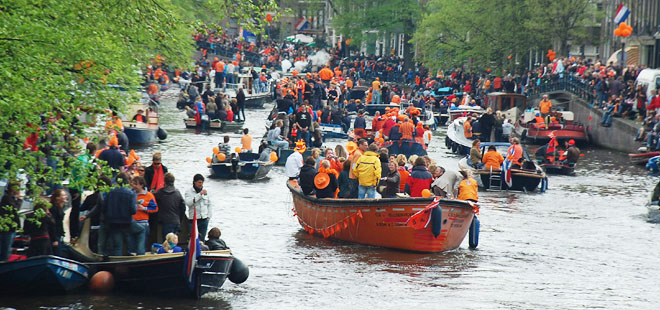 A canal full of celebrants on Queen's Day in Amsterdam, The Netherlands