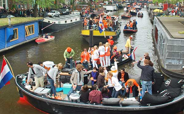 Amsterdam canal scene during Queen's Day party.